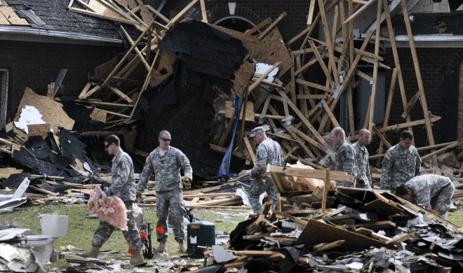 """Approximately 50 soldiers from the U.S Army John F. Kennedy Special Warfare Center and School at Fort Bragg volunteered to assist in the clean-up of a Fayetteville neighborhood, April 21, that had been damaged by tornadoes in the area. More than 60 tornadoes touched down across the state of North Carolina, April 16, damaging more than 400 homes and destroying more than 60. The group of soldiers spent the morning sorting through the debris and placing it in piles for pick-up by the city. The group was mainly comprised of recent Special Forces Qualification Course graduates awaiting assignment to their following unit. Residents provided yard equipment and once the debris was sorted, the soldiers began working on the landscape. Many homes in the relatively new subdivision were reduced to rubble. The normally well-manicured lawns looked like they were strewn with toothpicks, as splintered wood and roofing shingles lay spread across the grass. Many of the soldiers conducting the clean-up had prior experience with natural disaster recovery, such as Sgt. Luis Gutierrez, a recent SFQC graduate who was sent to assist in the clean-up in New Orleans after Hurricane Katrina in 2005. """"It just gives you a good feeling to be able to help out in a time of need."""""""