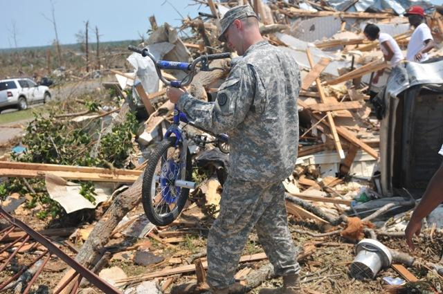 Spc. Robert Boettner, 31st Chemical Brigade, Northport, Ala., carries a child's bike from the rubble in the Crescent Ridge area in Tuscaloosa, Ala. Many families lost everything during the tornado and little discoveries like this bike that still works helps them to hold on to hope.